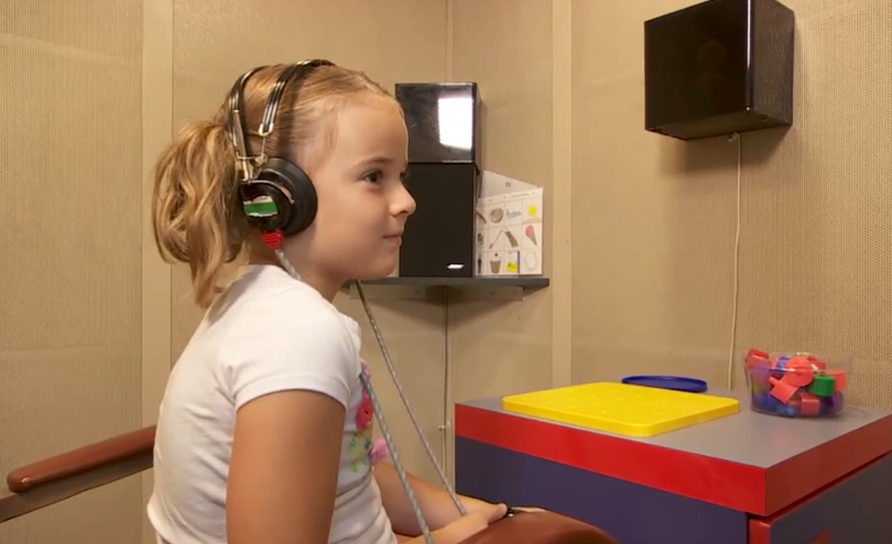 Young girl getting a hearing screening for school