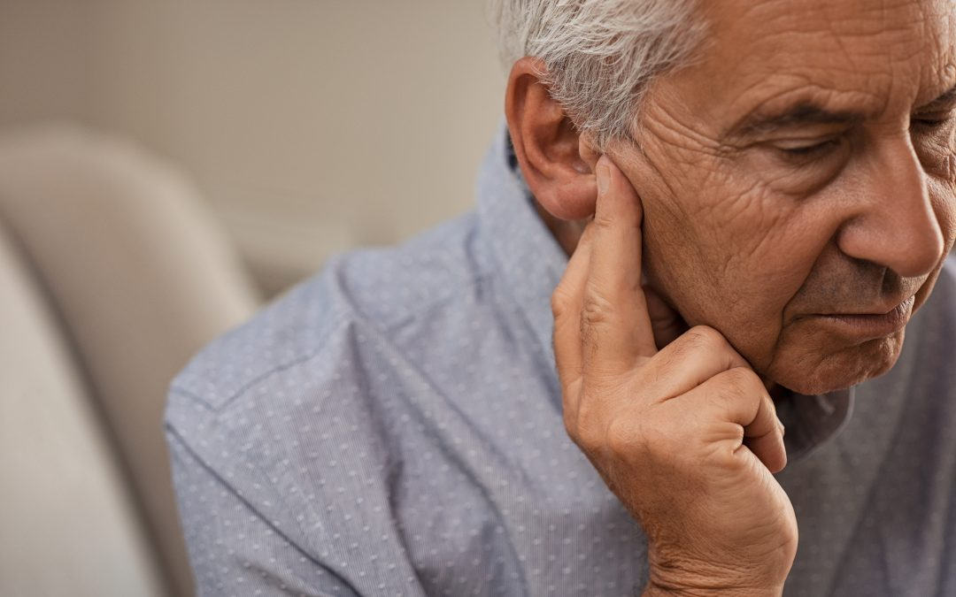 Side view of senior man with symptom of hearing loss.