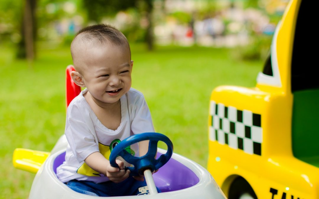 Baby playing in a toy car
